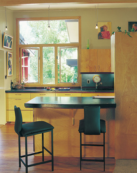 a mid century modern kitchen with light cabinetry and black bar stools