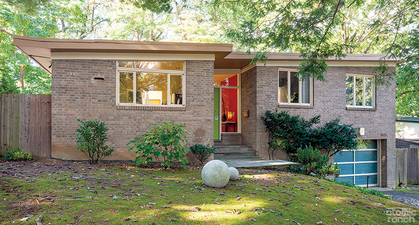 A mid century home featuring an Avanti garage door and stone balls in the front yard.