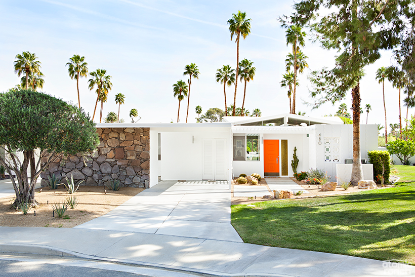 Palmer Krisel home featuring a textured white facade and an orange door as a part of the curb appeal ideas.