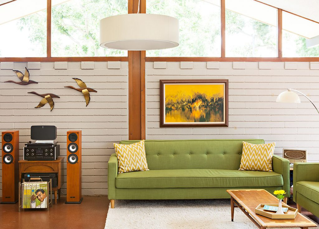 green couch against a cream colored painted concrete wall in a riverside mid century modern home