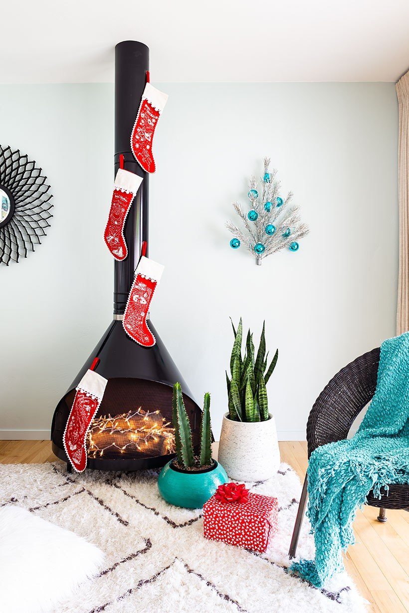 Mid Century Modern Malm fireplace decorated for Christmas with stockings and an aluminum Christmas tree.