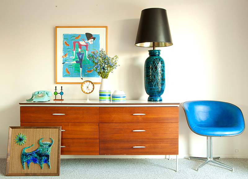A mid century modern walnut credenza with sleek oval pulls sit in a guest room in a Palm Springs home. A Bitossi lamp with a black shade as well as a Bitossi bull artwork both in a deep teal blue pop against cream walls.