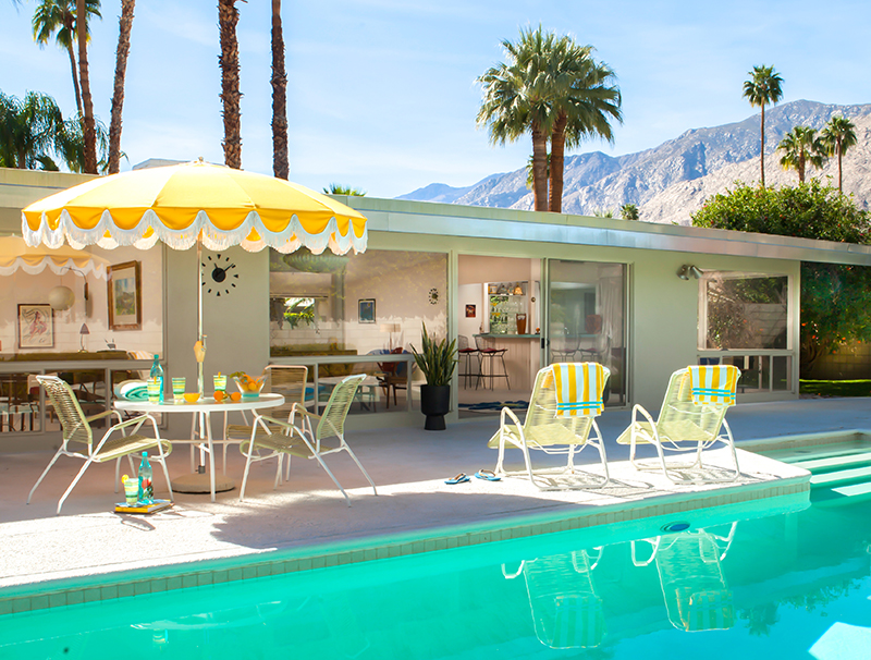 The backyard takes full advantage of the property's mature palm trees and stunning views, while deep overhanging South-facing eaves provide protection from the desert sun and heat. The pool's large size and proximity to the house is a Palm Springs trademark.