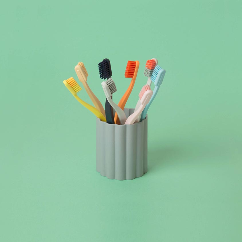 colorful modern toothbrushes in a grey fluted tumbler. Mid Century Modern bathroom upgrades.