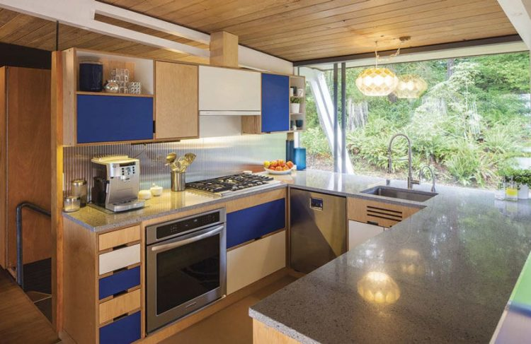 A mid century modern kitchen with a laminate countertop and wooden cabinetry.