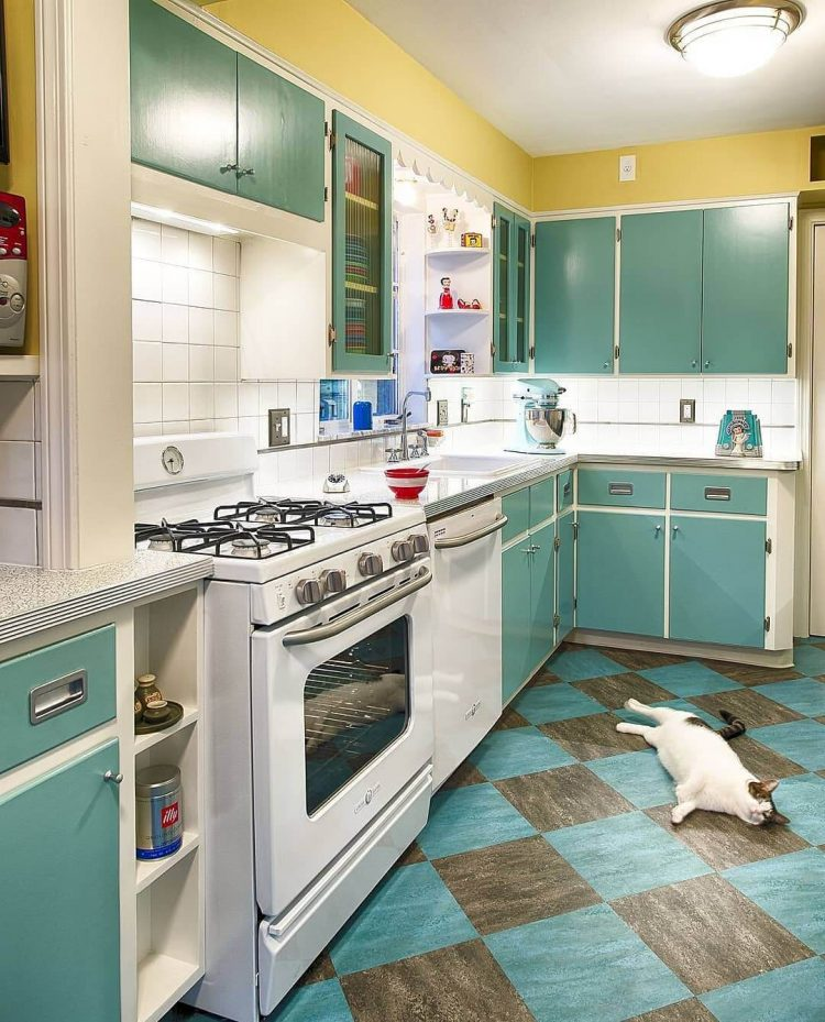 A mid century modern kitchen complete with a dark blue interior, diamond-shaped floor pattern, and cat laying on said floor.