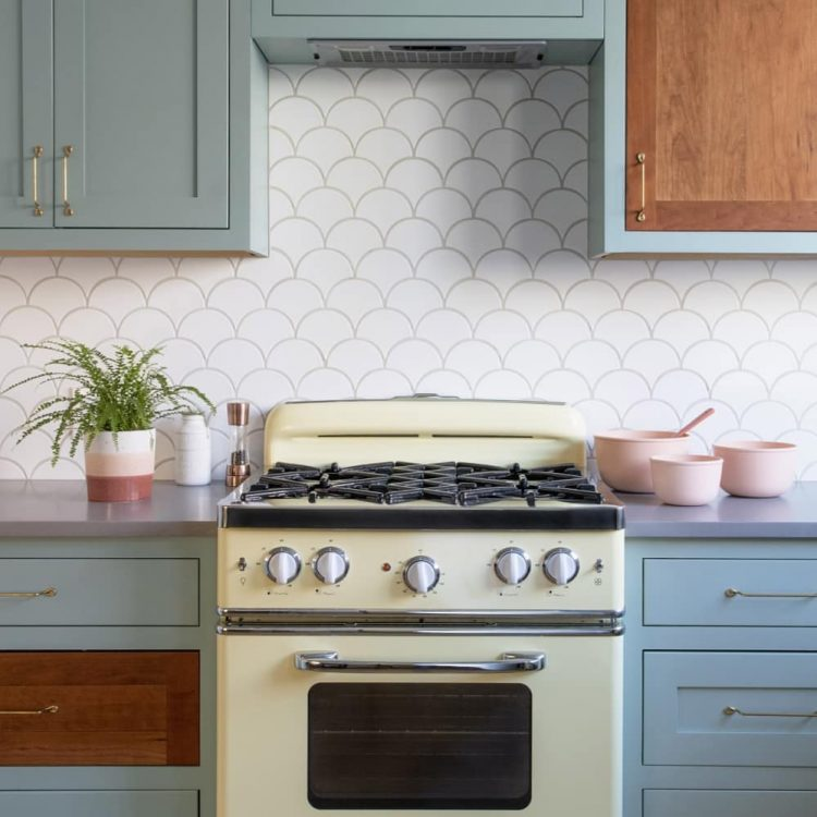 A mid century kitchen complete with a muted blue, yellow, and pink interior.
