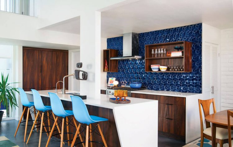 A mid century modern kitchen with a dark-blue geometric tile scheme, dark cabinetry, and slight vintage touches.