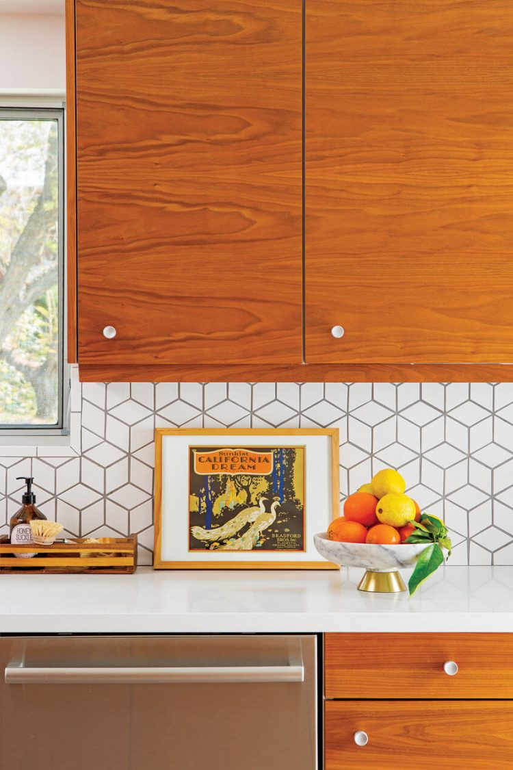 A mid century kitchen featuring a geometric-tile backdrop and a vintage poster to complement the surrounding spaces.