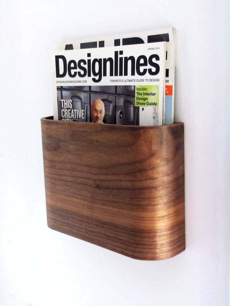 Mid century magazine rack with sleek wood exterior, mounted on a wall.