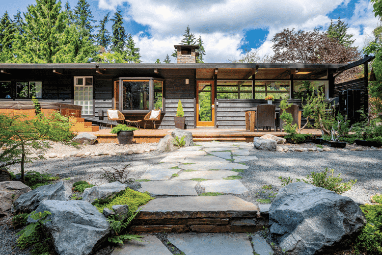 The backyard of this planar home with a rock-lain path and zen mid century style.
