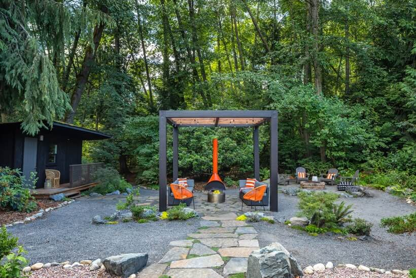 Backyard pergola with mid century style furniture in orange and modern firepit
