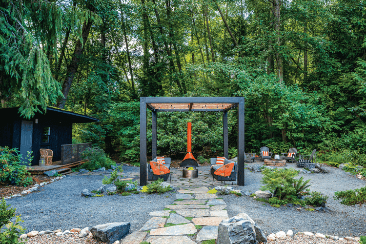 The mid century backyard complete with a rock-built path, freestanding orange fireplace and gazebo.