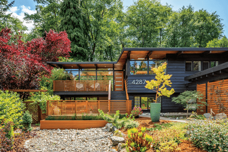 The caviar-painted exterior of this MCM home complete with wooden slats, the surrounding nature, and a mid century zen style.