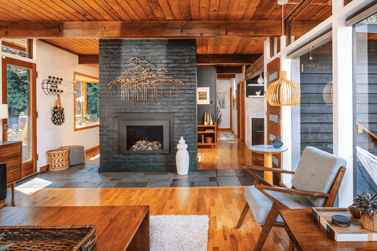The zen mid century living room boasting newly finished wood flooring and a central brick fireplace painted in a similar charcoal shade as the exterior.