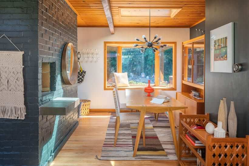 Dining area in mid century style home with brick fireplace, starburst chandelier and window seat