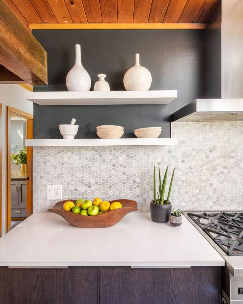 Kitchen countertop with black walls, hexagon backsplash and ceramic vases.