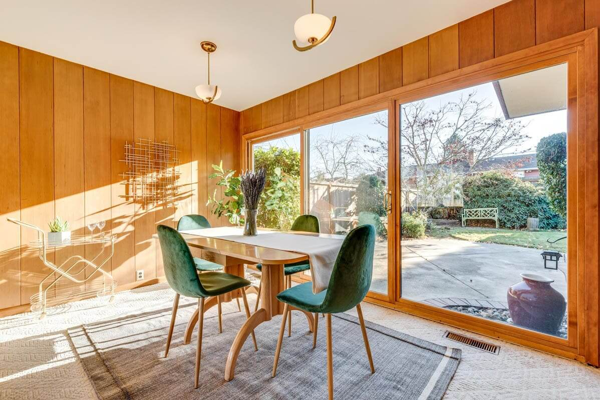 The dining area of this mid century home is accompanied by a view of the backyard thanks to floor to ceiling windows.
