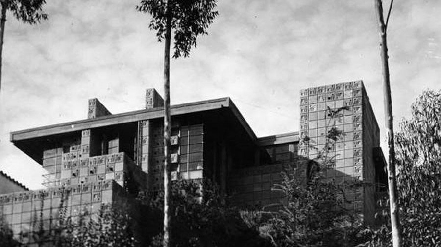 The Freeman House designed by Frank Lloyd Wright sits on a hill in Hollywood surrounded by palm trees.