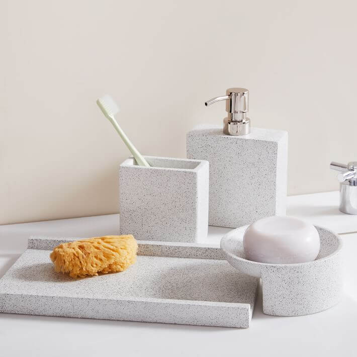 Cement-themed bathroom update with modern soap dispenser and toothbrush holder.