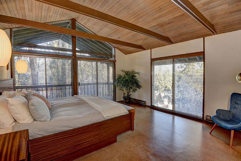 In the master bedroom, the east and north walls illuminate the room with daylight via the sliding glass doors and matching floor-to-ceiling plate glass windows.
