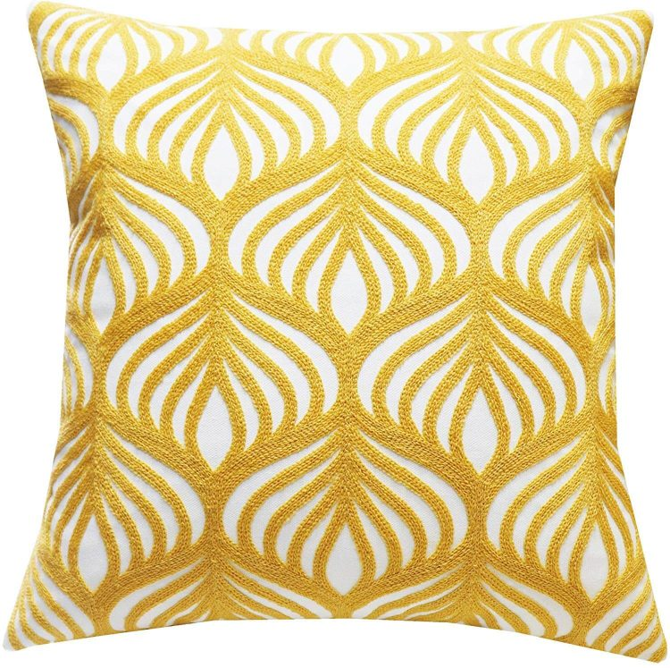 Living room and entertaining yellow pillow with interlinking geometric design.