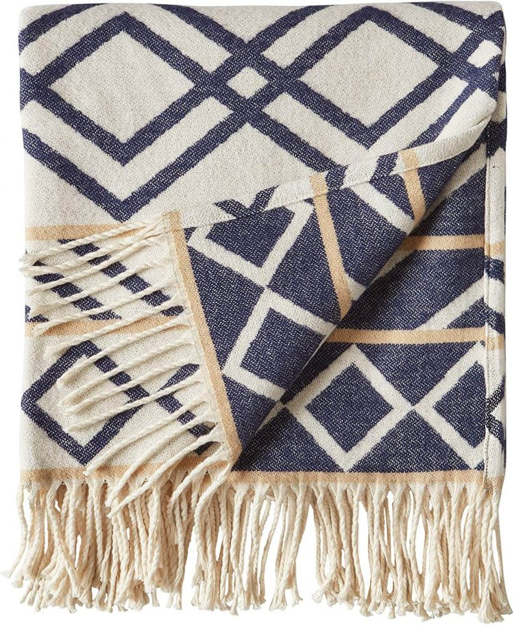 Blanket with blue geometric designs and tassles.