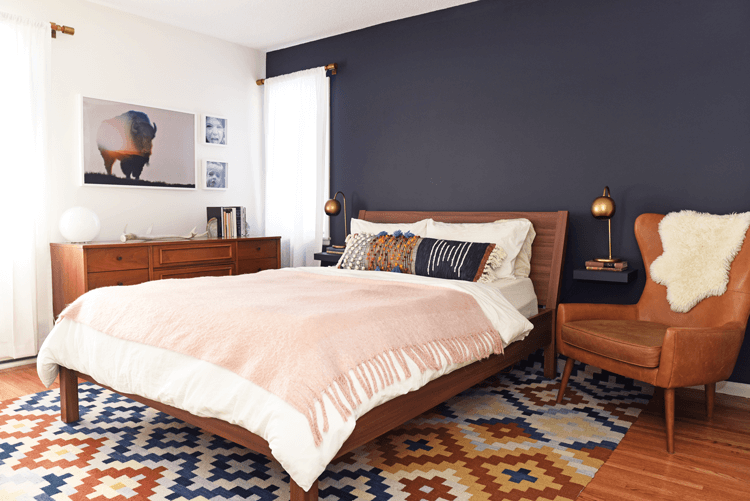 The dark, inky hue of the mid century modern master bedroom's feature wall anchors the space, while the warm tones of walnut-stained wood furnishings and cognac -colored leather upholstery create cohesion.