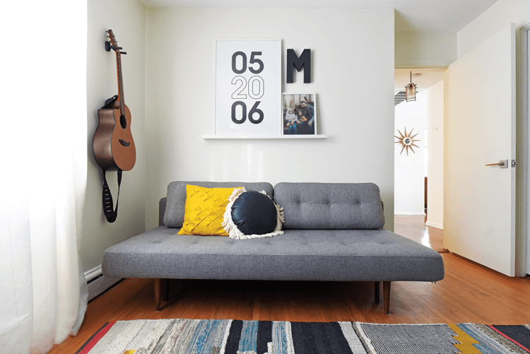 A Mid Century Modern daybed in an office with a guitar hanging on a nearby wall.