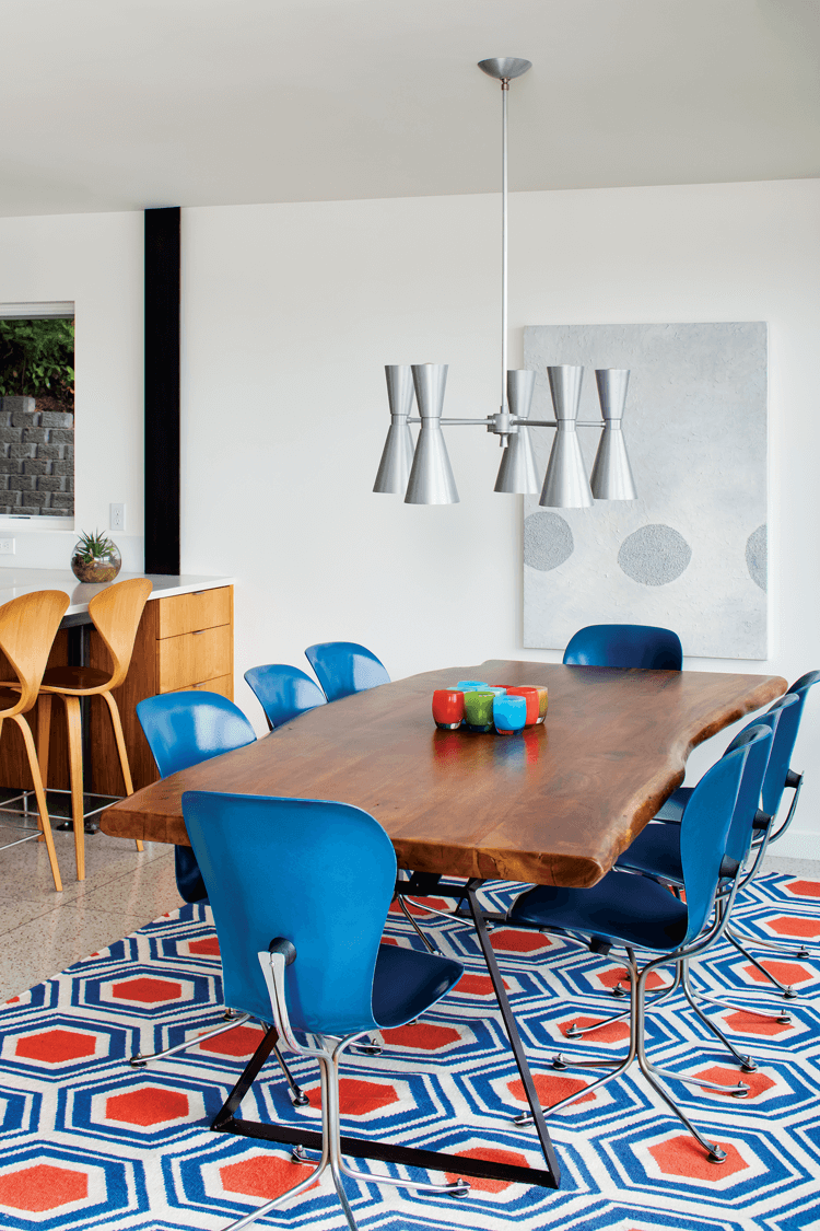 A Midcentury Modern dining set with a live-edge table, blue chairs and a retro print rug in blue and orange.