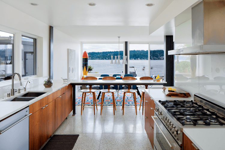 A Mid Century Modern kitchen with lake views, a mid century dining set and a World War II test bomb as decoration