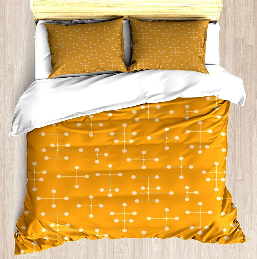 mid century modern bedding set in an goldenrod color sporting an atomic eames pattern in white