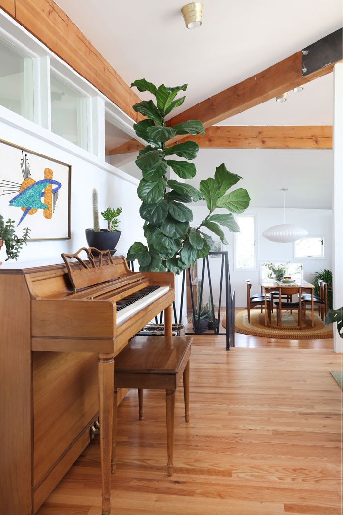 Clerestory windows above a piano in a mid century modern living room