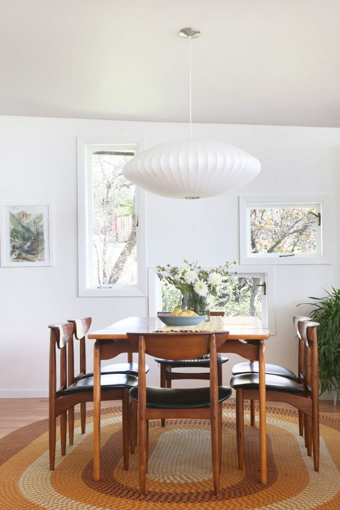 Mid Century Modern dining room in a post and beam house with Nelson saucer pendant lamp.