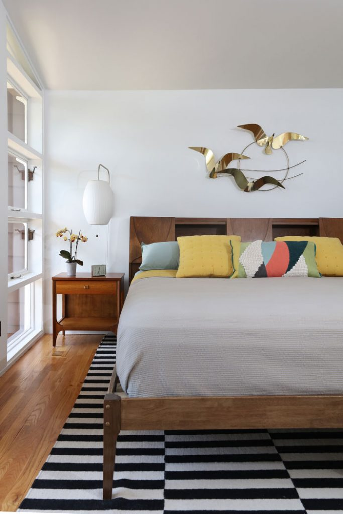 Vintage Curtis Jere birds soar above a rare Broyhill Brasilia bookcase headboard and matching side table.