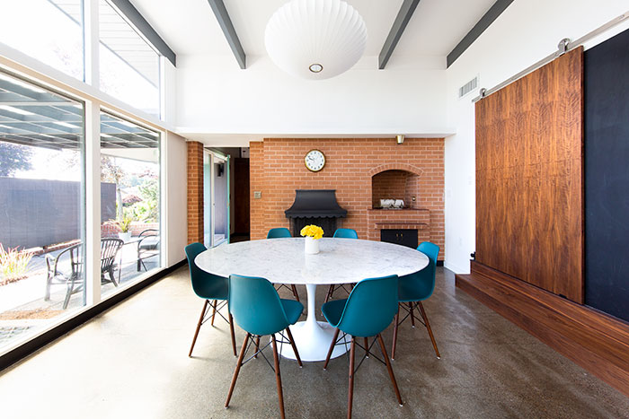 Mid Century Modern dining room with brick fireplace in a midcentury modern renovation in oregon