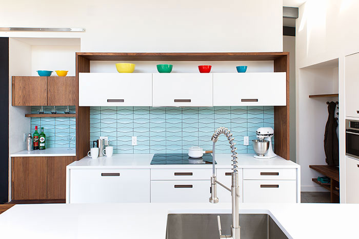 Mid Century Modern kitchen renovation with walnut finishes and blue tile backsplash