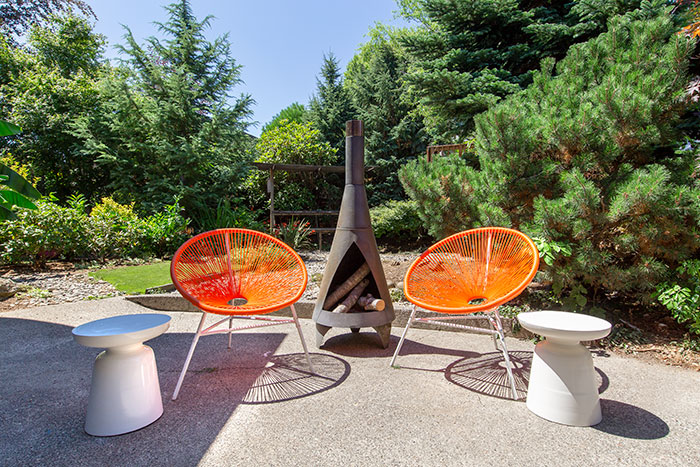 Mid Century Modern Backyard with orange chairs and wood-burning fireplace
