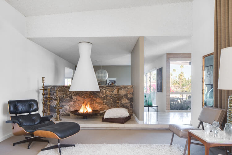 Desert Modern interior with rock feature wall, white fireplace, and Eames lounger
