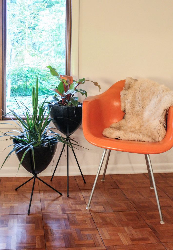two black bullet planters placed in front of a window beside an orange Eames chair.