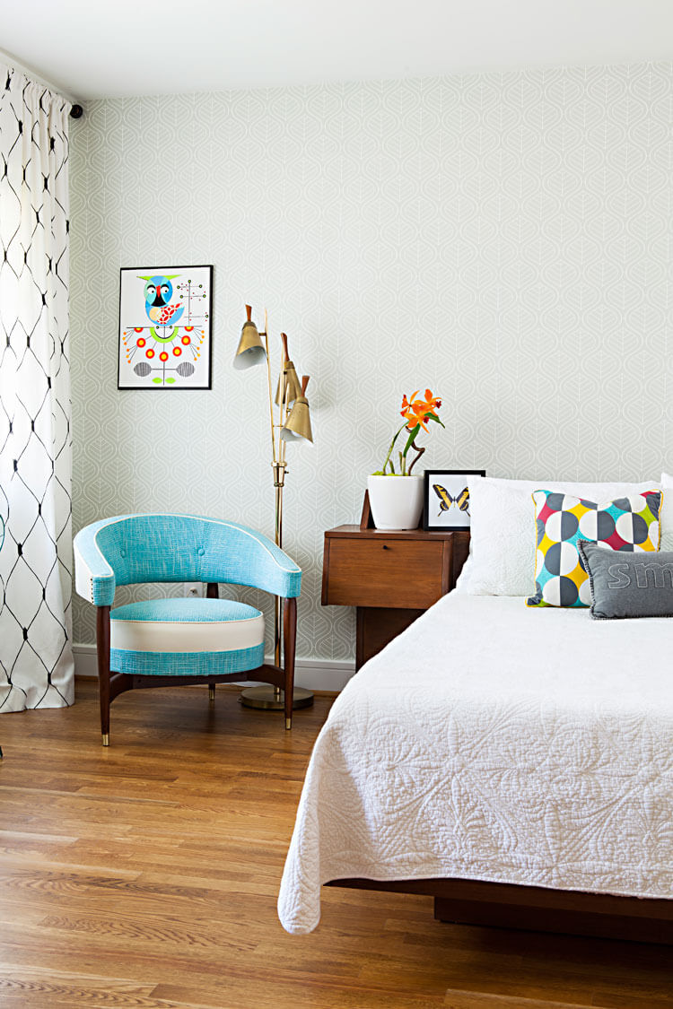 bedroom with A ben with white quilt, wood flooring and light blue arm chair. Pops of color appear with flowers in a vase, a modern wall art piece and a patterned pillow.