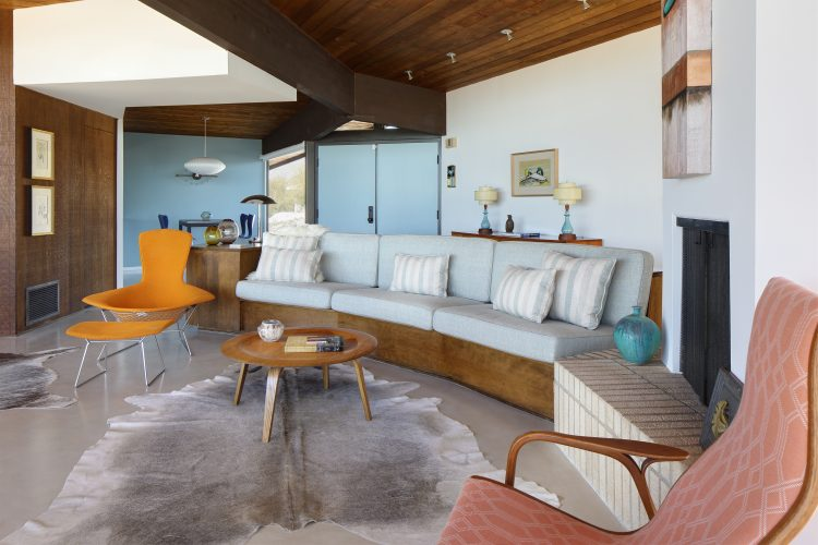 Living room with vintage blue couch and orange egg chair in restored arthur t. brown house