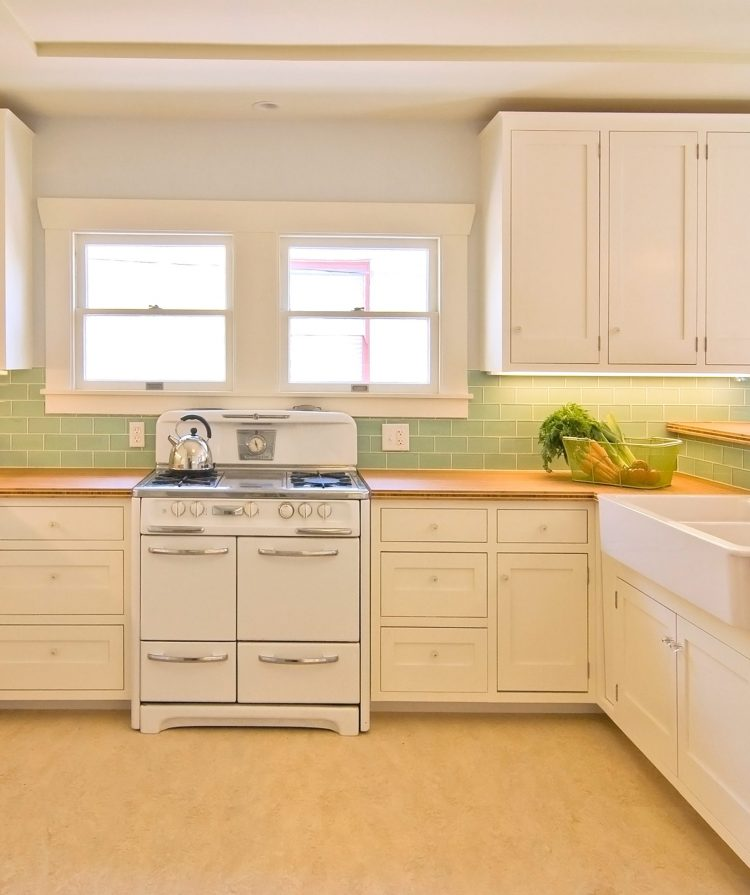 green subway tile from modwalls in a mid century modern kitchen with a window and farmhouse sink