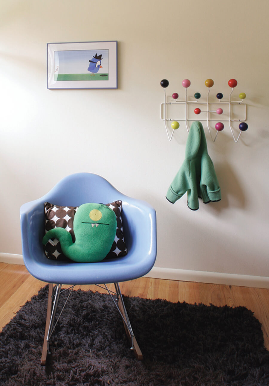 A monster stuffed animal on a mod purple molded plastic rocking chair with a cartoon bird wall art piece behind it. A child's coat hangs from an Eames Hang-It-All Coat Rack
