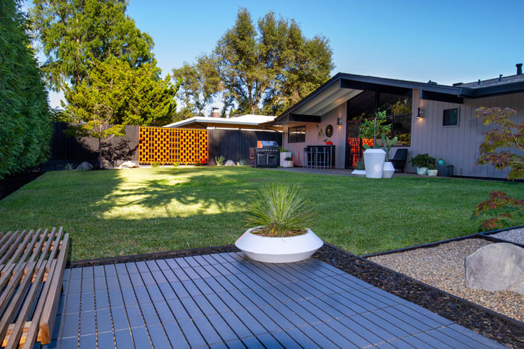 Mid Century Modern backyard with mod planters and grass lawn