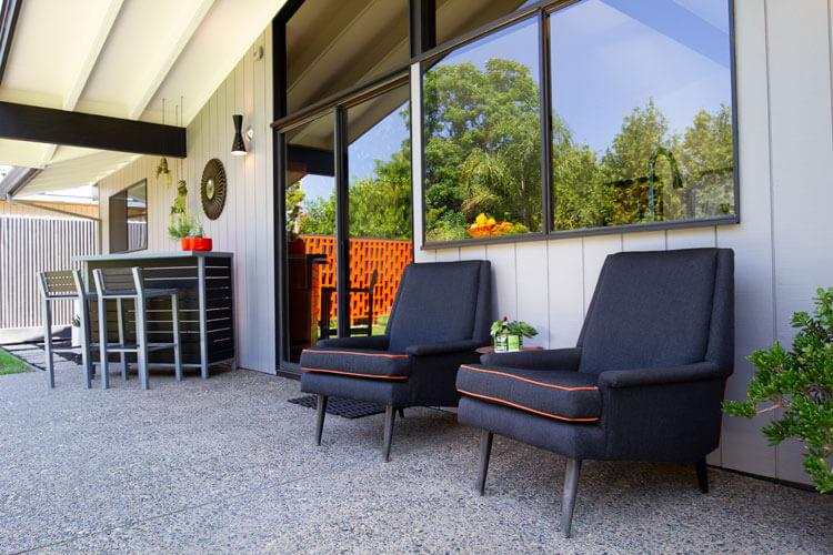 Mid Century Modern outdoor armchairs on a backyard patio