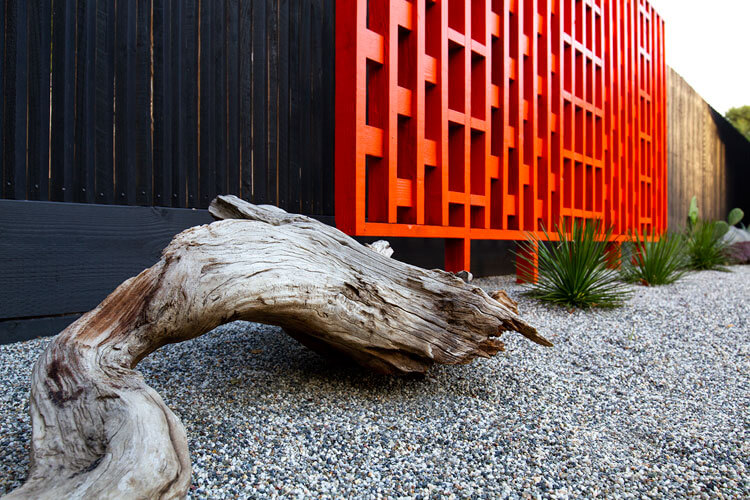 Tri-stake fence in black in the mid century modern backyard with an orange feature screen.
