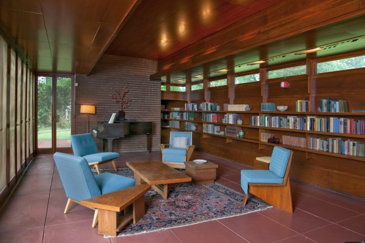 Usonian living room with a three-shelf bookcase built into the back wall. Four modern chairs make up the room accented with a large statement rug. Floor to ceiling windows.