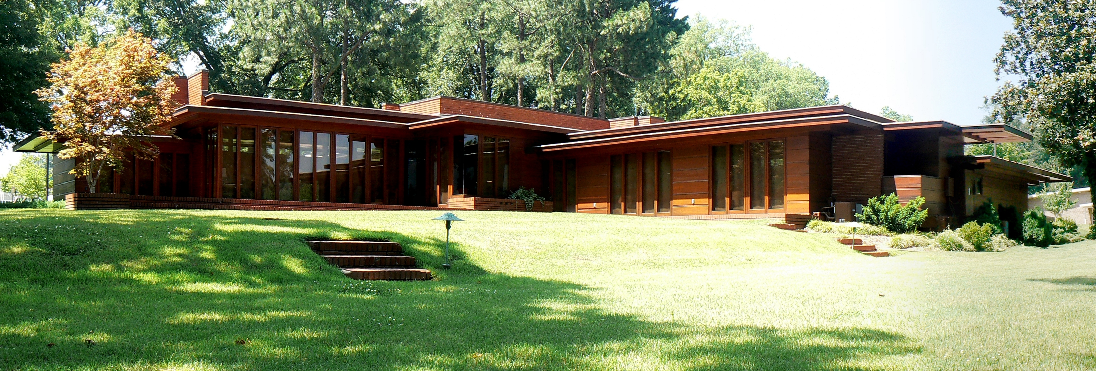 The front exterior of a usonian ranch house with floor to ceiling windows surrounded by trees and grass.