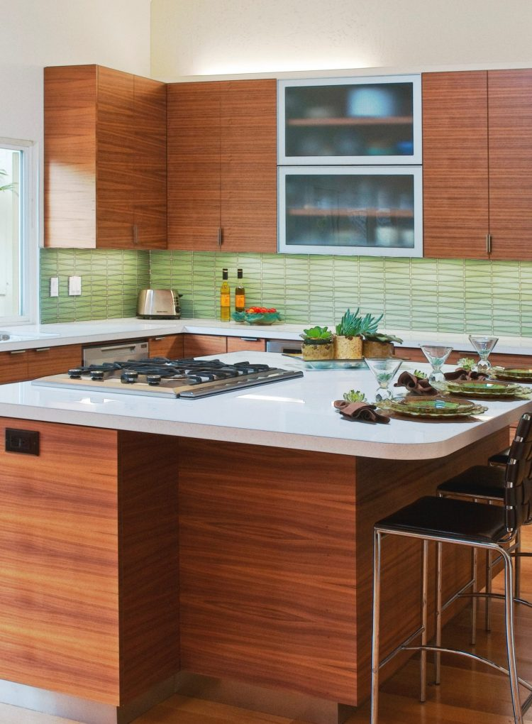 Green mid century modern tiles from modwalls in a kitchen with dark cabinets and light countertops